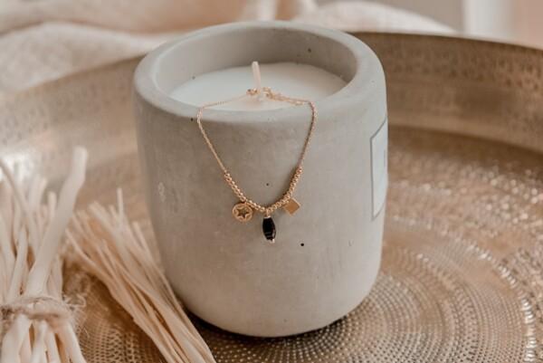 Armband goud met bedeltjes en zwart steentje