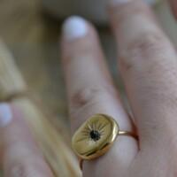 Onregelmatig gevormde ring goud met zwart steentje aan hand onbewerkt